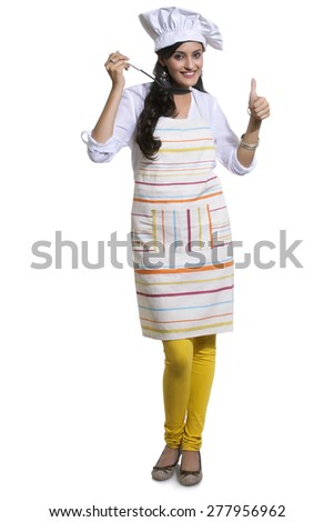 Portrait of a female chef tasting and giving thumbs up sign - stock photo