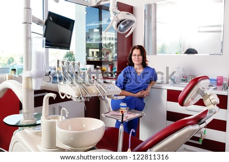 Portrait of a female dentist in the operating room - stock photo