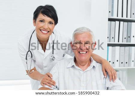Portrait of a female doctor with happy senior patient at the hospital - stock photo