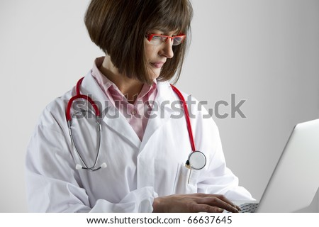 Portrait of a female doctor with laptop - stock photo