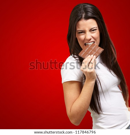 Portrait Of A Female  Eating Chocolate On Red Background - stock photo