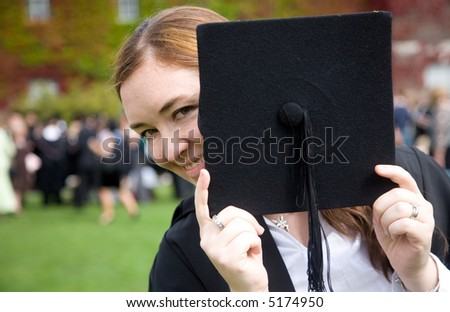 portrait of a female graduating at university hiding behind her hat