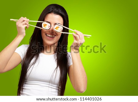 Portrait Of A Female Holding Sushi Roll On Green Background - stock photo