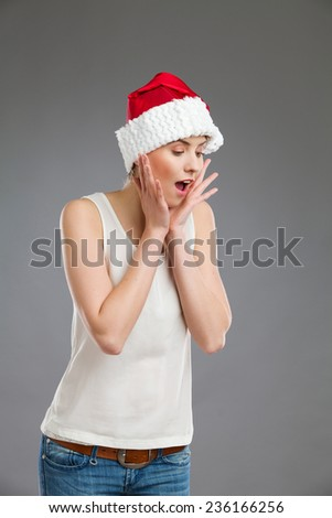 Portrait of a female in santa's hat with head in hands and looking down. Waist up studio shot on gray background. - stock photo