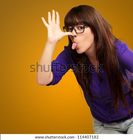Portrait of a female making funny face on yellow background - stock photo