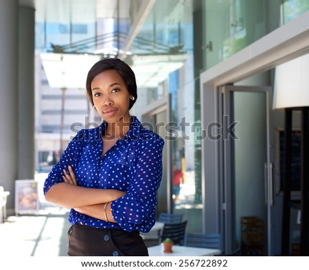Portrait of a female office worker standing outside business building - stock photo