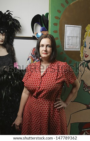 Portrait of a female owner standing by costumes at the second hand store - stock photo