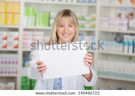 portrait of a female pharmacist showing white paper - stock photo
