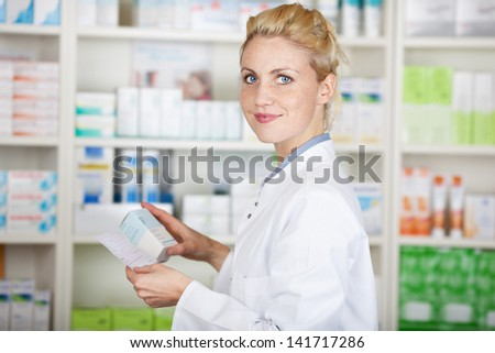 Portrait of a female pharmacist with prescription in front of medicines at drugstore - stock photo