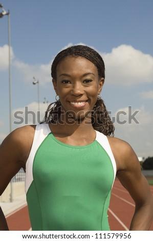Portrait of a female runner in sportswear on athletic field - stock photo