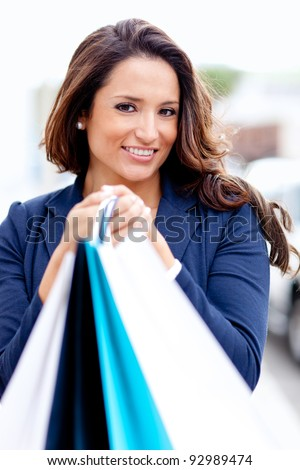 Portrait of a female shopper holding bags and smiling - stock photo