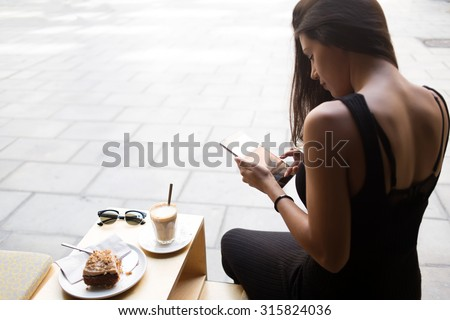 Portrait of a female student using touch pad while sitting in coffee shop outdoors, freelancer girl working on her digital tablet with copy space screen, hipster woman browsing on touchscreen device - stock photo