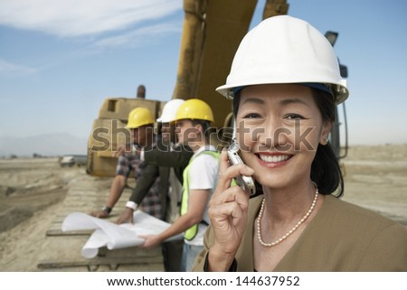 Portrait of a female surveyor in hard hat in front of heavy machinery using cellphone on site - stock photo