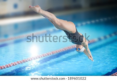 Portrait of a female swimmer, that jumping and diving into indoor sport swimming pool. Sporty woman. - stock photo