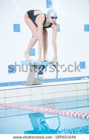 Portrait of a female swimmer, that wearing a swimming cap and goggles and preparing to jump into swimming pool. Sporty woman. - stock photo