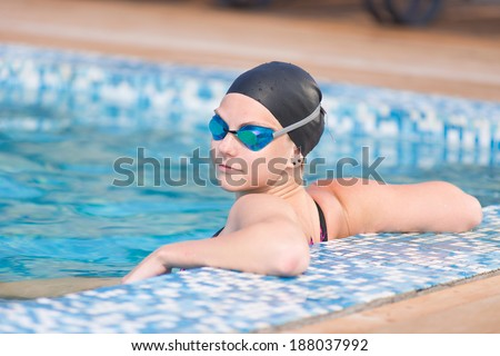 Portrait of a female swimmer wearing a swimming cap and goggles in blue water swimming pool. Sport woman. - stock photo