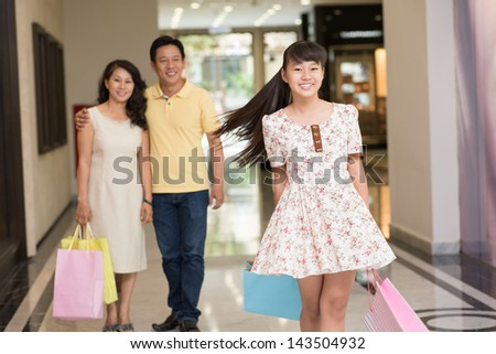 Portrait of a female teenager at shopping with her parents