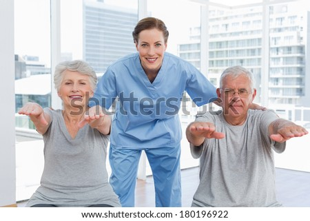 Portrait of a female therapist assisting senior couple with exercises in the medical office