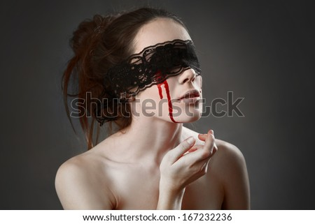 Portrait of a female vampire with black lace on her eyes - stock photo