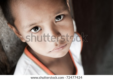 Portrait of a Filipino boy living in poverty - natural light - Manila, Philippines. - stock photo