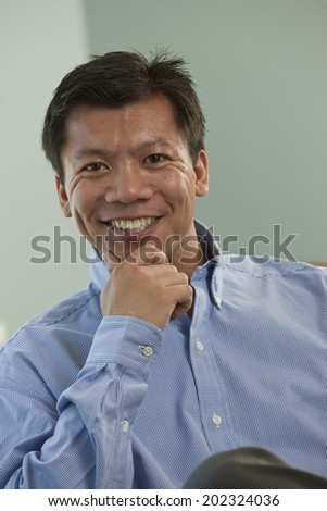 Portrait of a Filipino business executive seated in a conference room with his hand holding his chin. - stock photo