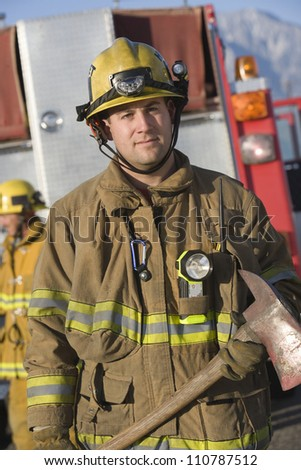 Portrait of a firefighter holding an axe - stock photo
