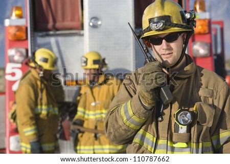 Portrait of a firefighter talking on radio with colleagues standing in the background - stock photo