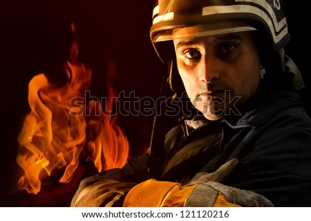 Portrait of a fireman with fire isolated in black - stock photo