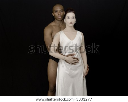 Portrait of a fit couple on black studio background.  Representative of diversity. - stock photo