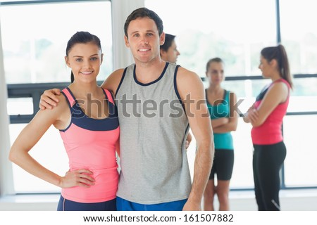 Portrait of a fit couple with friends standing in background in bright exercise room - stock photo