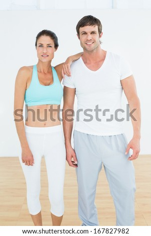 Portrait of a fit young couple standing in fitness studio - stock photo