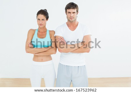 Portrait of a fit young couple with arms crossed standing in fitness studio - stock photo