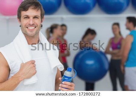 Portrait of a fit young man holding water bottle with friends in background at fitness studio - stock photo