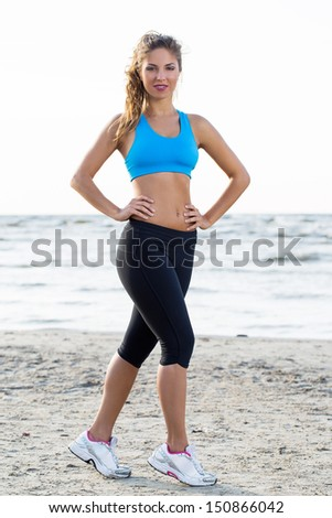 Portrait of a fitness girl who is doing her workout near the sea - stock photo