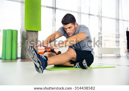 Portrait of a fitness man doing stretching exercises at gym  - stock photo