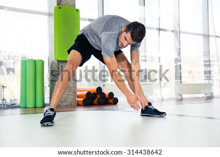 Portrait of a fitness man warming-up at gym  - stock photo