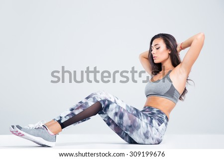Portrait of a fitness woman doing abs exercises isolated on a white background - stock photo