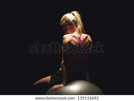 Portrait of a fitness woman sitting on a pilates ball and having her workout break - stock photo