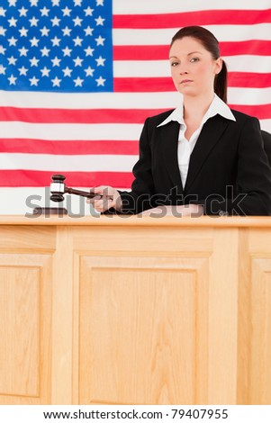 Portrait of a focused judge knocking a gavel looking at the camera - stock photo