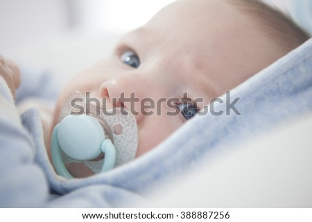 Portrait of a four months old baby with pacifier. Selective focus - stock photo