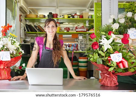 Portrait of a friendly and welcoming florist business woman owner proudly standing at the counter of a flower store using a laptop computer, smiling. Small business technology. - stock photo