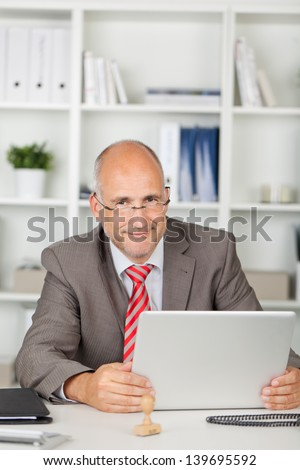 portrait of a friendly businessman sitting at desk with laptop - stock photo