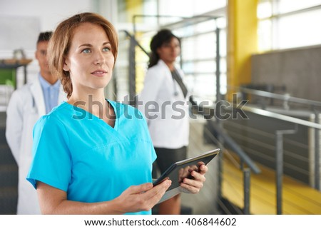 Portrait of a friendly caucasian female doctor and team in bright modern office - stock photo