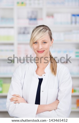 Portrait of a friendly female pharmacist with crossed arms with the medicine shelves in the background