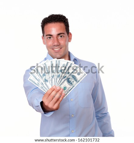 Portrait of a friendly man on blue shirt standing and holding up dollars while is smiling at you on isolated background