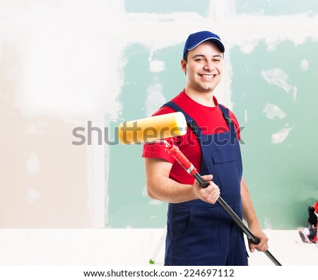 Portrait of a friendly painter at work in an apartment - stock photo