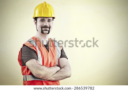 Portrait of a friendly worker with yellow hard hat - stock photo