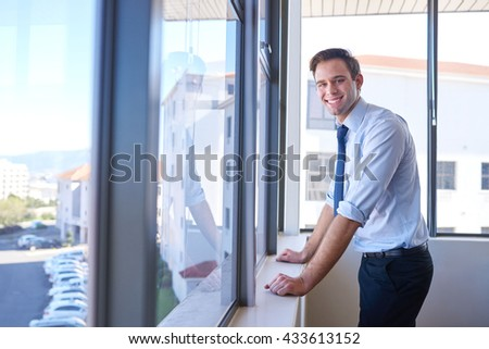 Portrait of a friendly young businessman standing at the windows in his office, smiling at the camera - stock photo