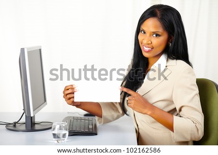 Portrait of a friendly young executive lady at work while show a white card