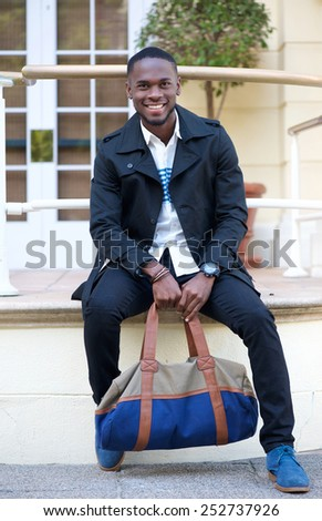 Portrait of a friendly young man sitting outside hotel with bag - stock photo